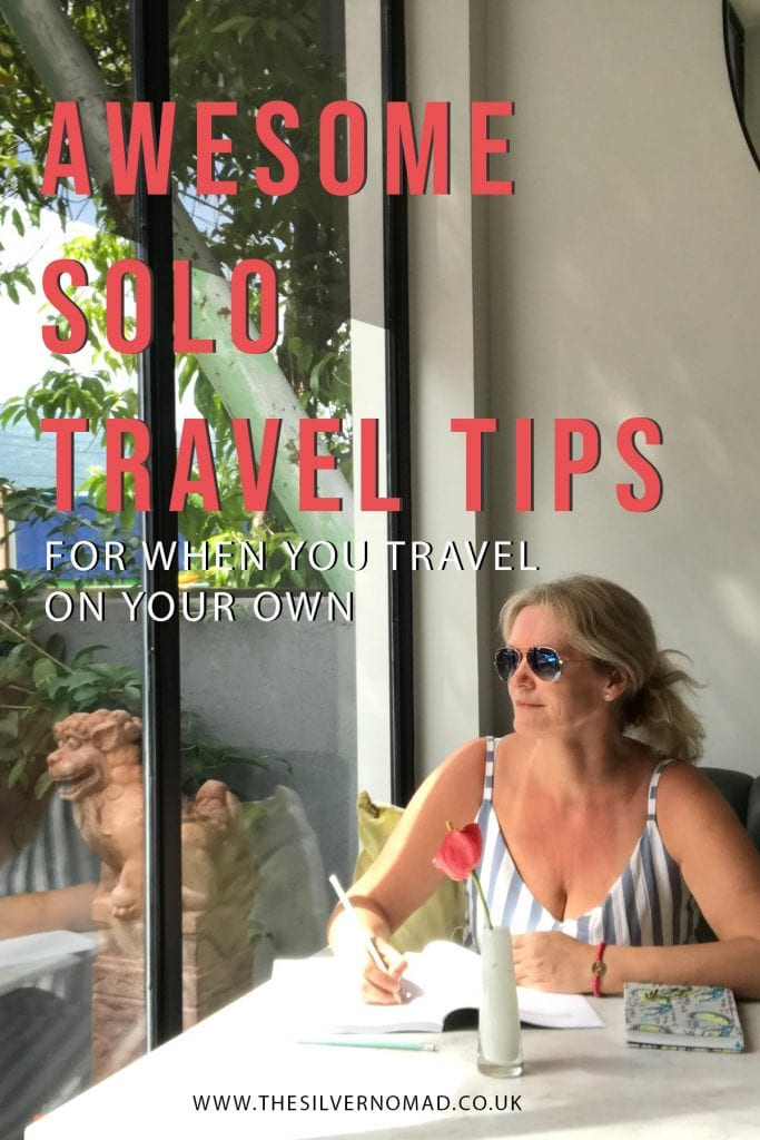 Woman wearing a stripped sleeveless dress and sunglasses looking out a window with the words Awesome Solo Travel Tips superimposed