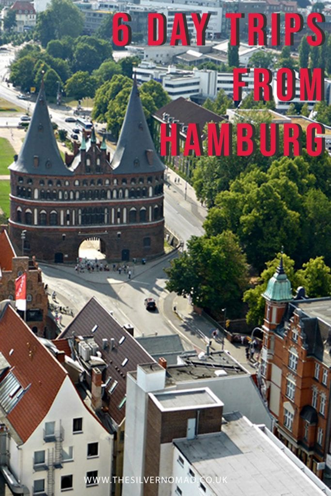 image of a turreted buildings with trees round it and other buildings in the foregorund with the words 6 day trips from Hamburg superimposed