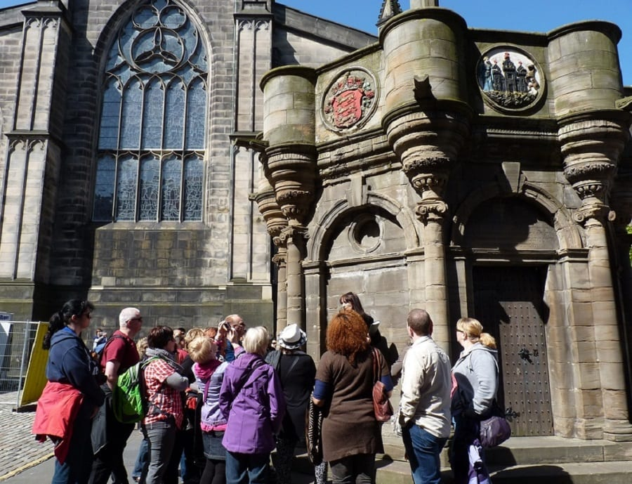 A group of people standing outside Scottish Church in Edinburg - a great solo travel tip for meeting people