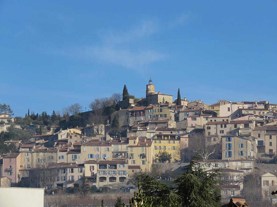 View from below of the hilltop town of Fayence, showing the terraces of cream coloured buildings with red roofs against a blue sky