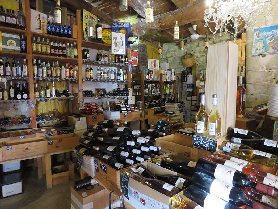 The inside of La Cave de Fayence with rows of bottles of wine on shelves and on tables. Red white and rose wine bottles