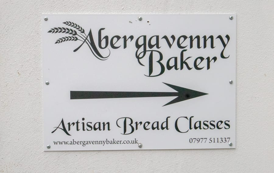 White sign on white wall with black writing saying Abergavenny Baker the A has three wheat ears coming off to the left.  Below is a black arrow pointing to the right and Artisan Bread Classes below