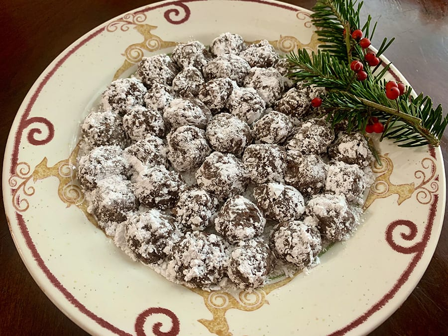 Cream plate with red swirls with a pile of bourbon balls with some holly on the side