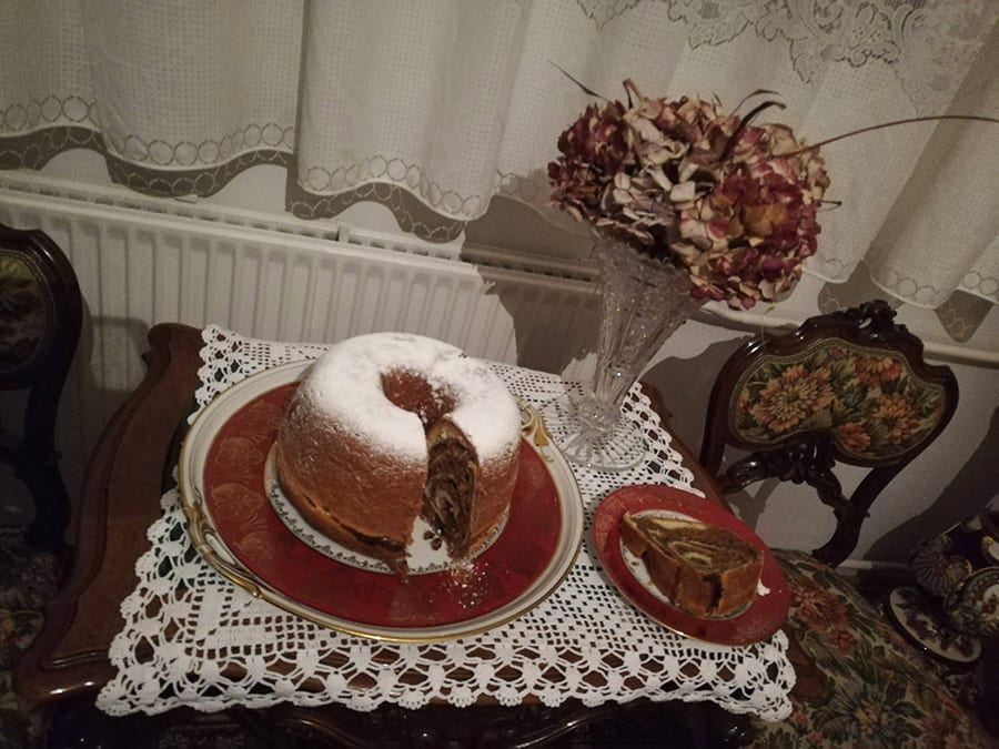 round marbled potica cake from Slovenia dusted with icing sugar and sitting on a red plate. The table has a lace tablecloth and there is dried flowers and net curtains in the background