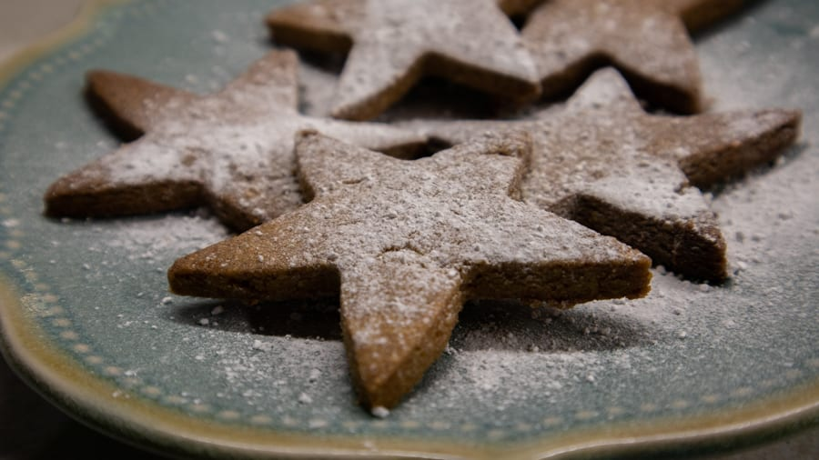 blue plate with star-shaped Dutch Christmas biscuits dusted with icing sugar