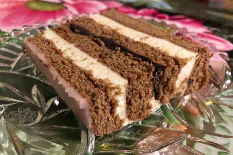 A glass plate with piernik - a polish gingerbread - on it with layers of semolina custard, gingerbread and pink frosting on top