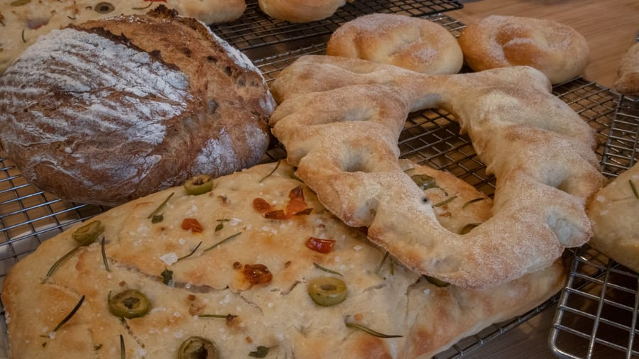 Brown loaf, fougasse bread with holes in it and focaccia with loives, tomatoes, salt and rosemary sitting on wire cooling racks