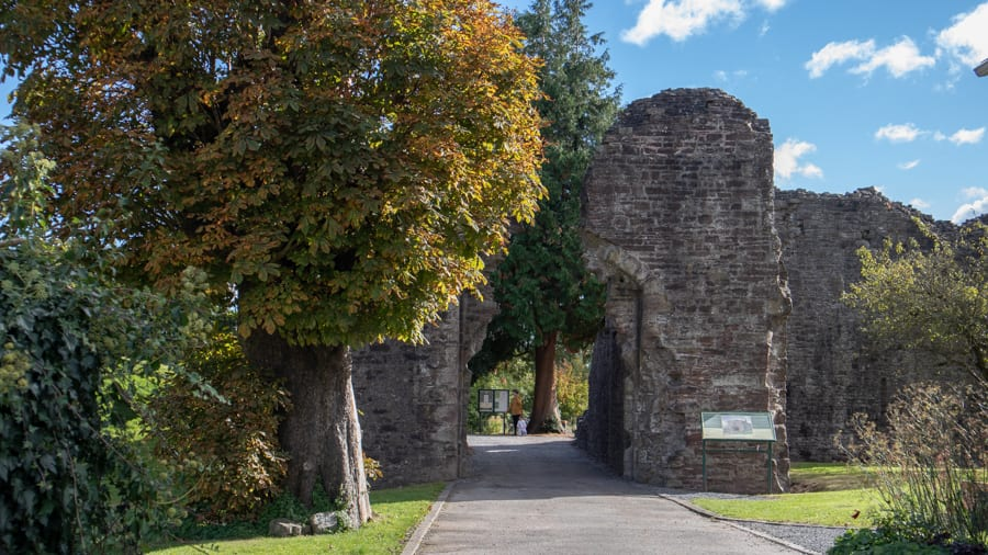 ruins at the entrance of Abergavenny Castle with trees on the left and grass and plants on the right one of the things to do in Abergavenny