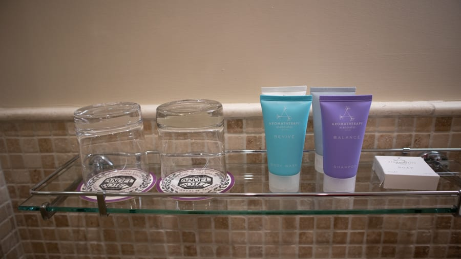 Glass shelf with two glasses and a turquoise, purple, white and blue tubes of Aromatherapy Associates