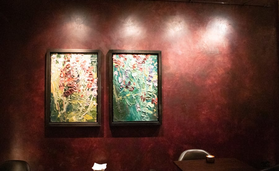 Two colourful Abstract paintings on a ruby red wall highlighted from above