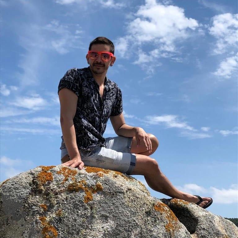Man wearing red sunglasses and a navy shirt and pale denim shorts sitting on a lichen covered rock with a blue sky and a few white clouds behind