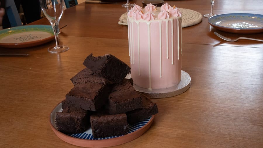 plate piled high with chocolate brownies next to a tall pale pink column cake with white chocolate drips down the sides and pink swirls on top