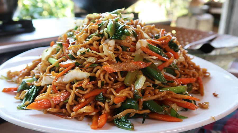 white plate of noodles with sliced carrots, cabbage and spring onions