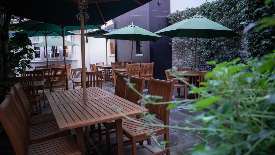 wooden patio furniture with green umbrellas on the outdoor patio at the Angel Hotel Abergavenny. There is a stone wall covered in ivy to the right and the