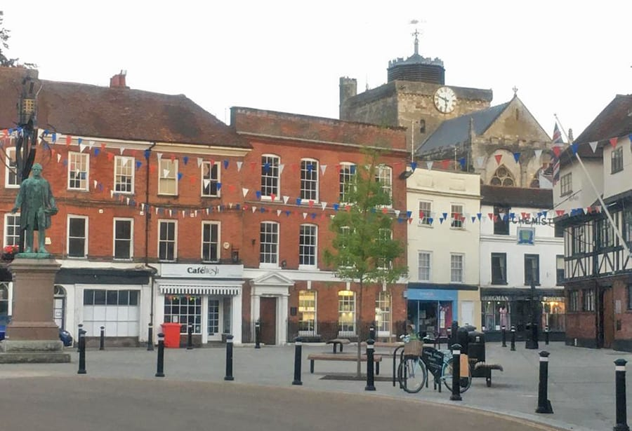 Market square with a Romsey Abbey in the background. There is blue, red and white bunting between the buildings