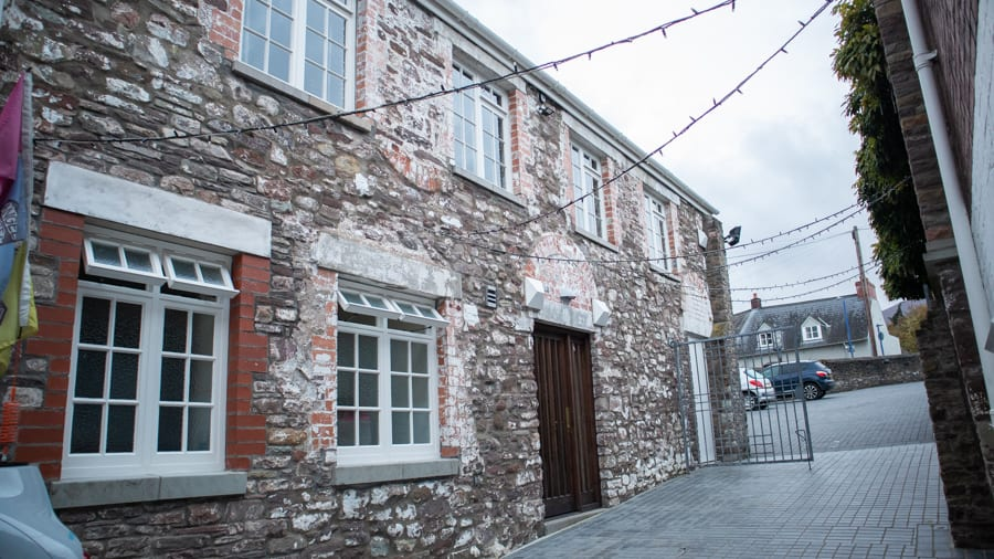 Stone and brick building with wooden door two windows with 8 panes downstairs and four upstairs. At the end of the building is a gate leading to the Angel Hotel Abergavenny car park