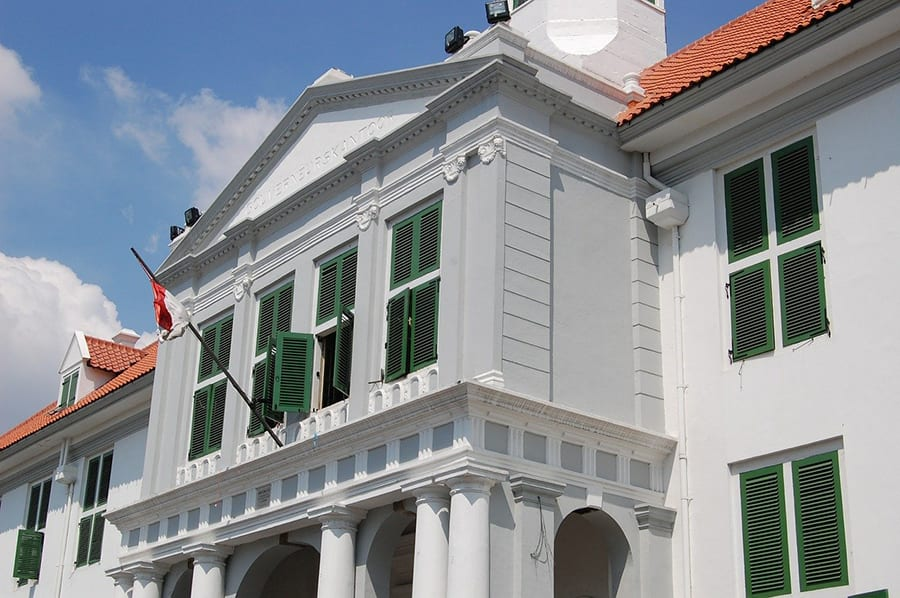 White building with green shutters and red roof flying the Indonesian flag