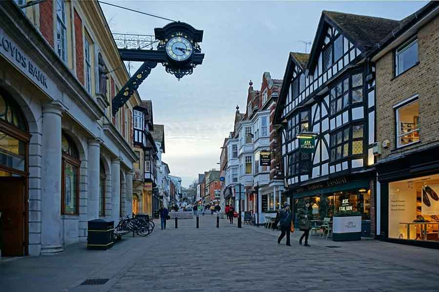 street with Tudor black and white building on the right and an ornate black and gold clock