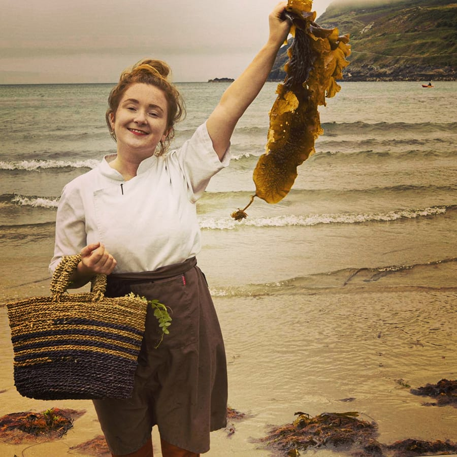 woman with a basket on one arm and holding seaweed aloft in the other on a beach with waves coming in behind