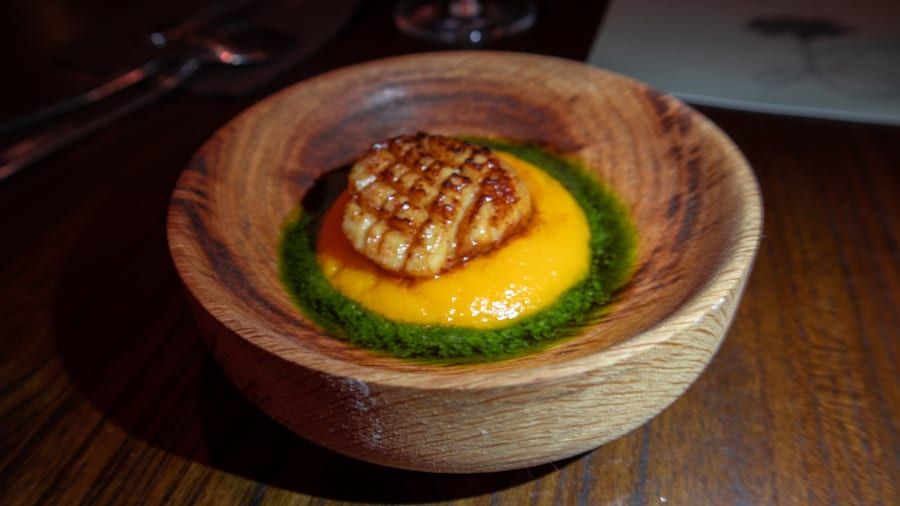 seared scallop with carrot purée and wild garlic in a wooden bowl