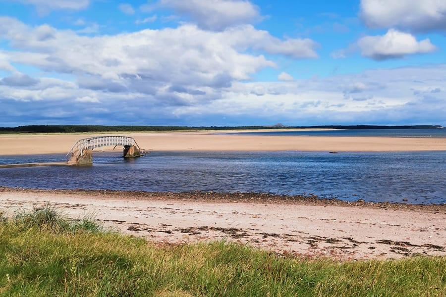 sandbars on a beach with sea flowing under a bring between two sandbars