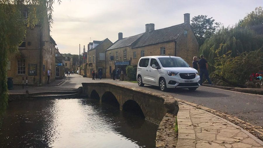 Bridge over the river in Bourton on the Water in the Cotswolds, with cream stone houses in the background