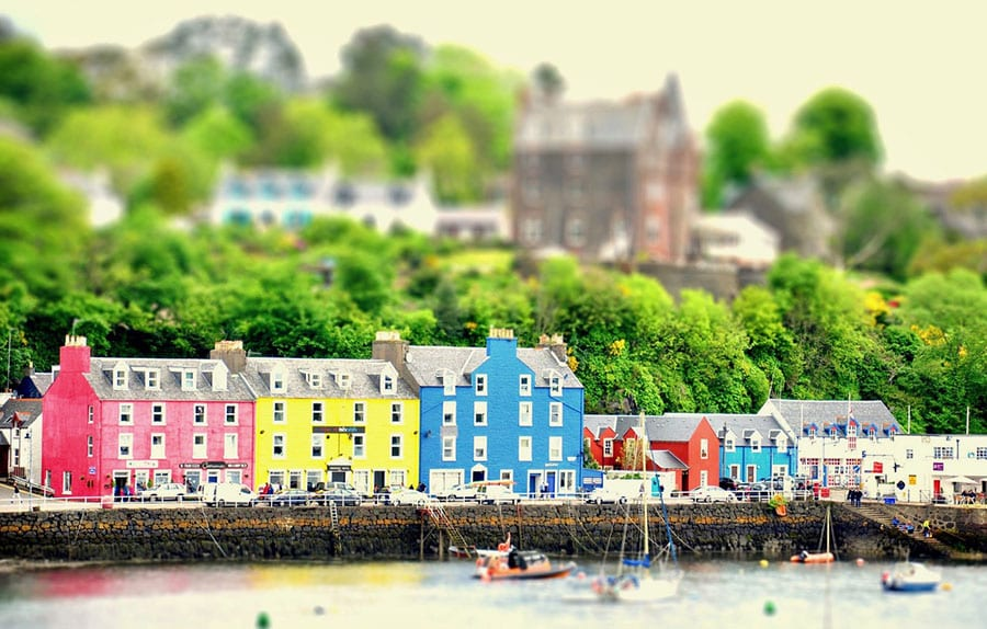 red, yellow, blue and oranges houses on the bank of the sea with boats in front and houses blurred in the background