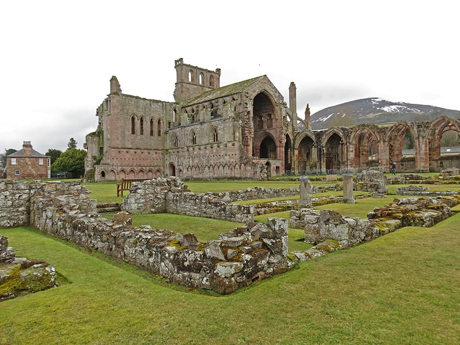 ruins of Melrose Abbey with large arches and hill in the background with a touch of snow