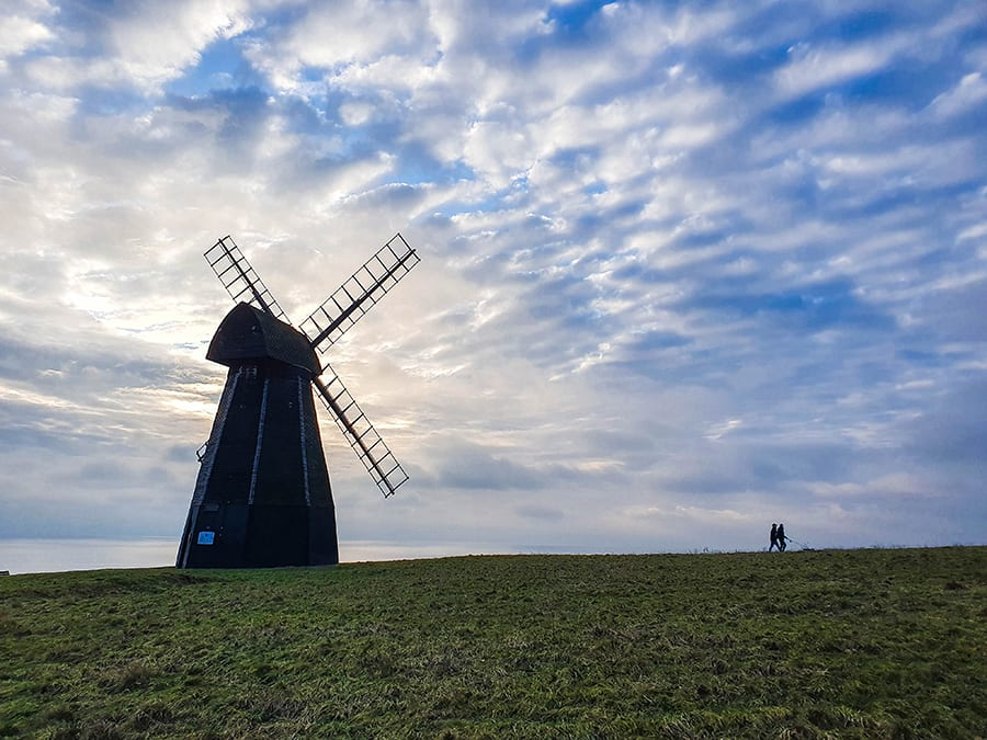 windmill standing on its own against a blue sky with two people walking away from it