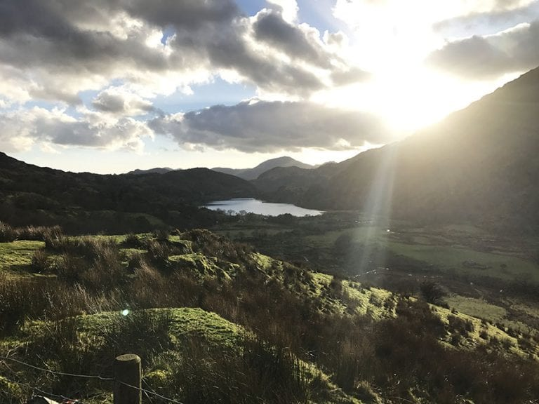 hills surrounding a lake in Snowdonia with the sun coming out behind the clouds
