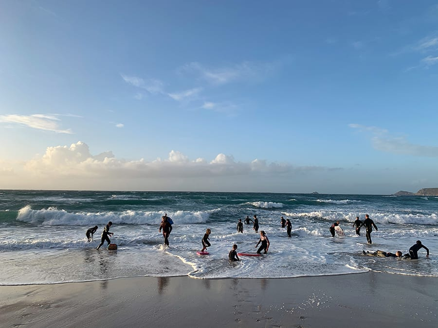 people in wet suits with body boards in the surf in Cornwall
