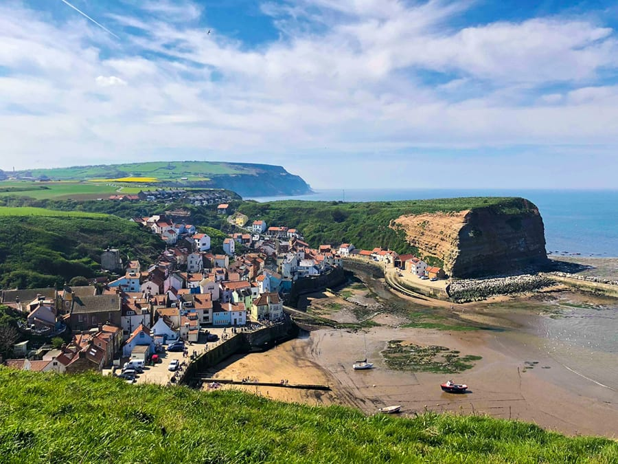The port of Staithes with houses on the left and cliff and see to the right