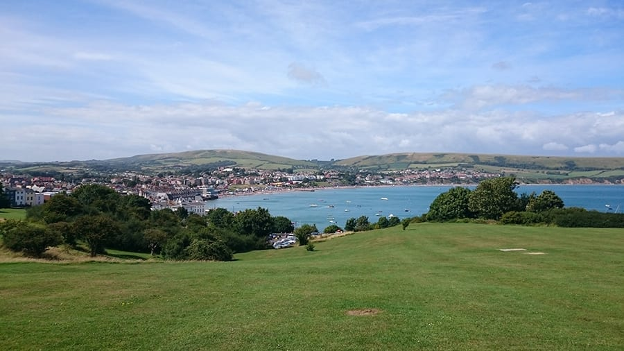 green grass overlooking a bay and the town of Swanage