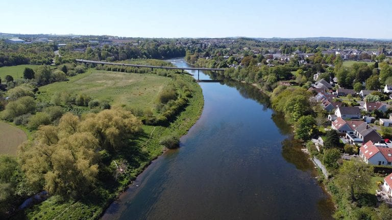 aerial view over the river Tweed with green fields on the left and houses on the right