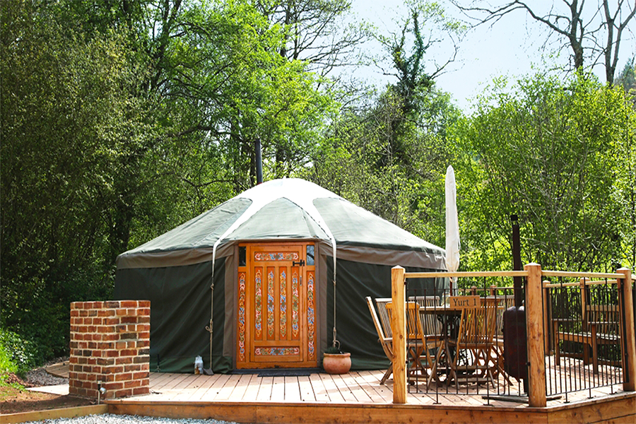 Yurt with traditional door sitting on a wooden patio with table, chairs and umbrella with trees in the background
