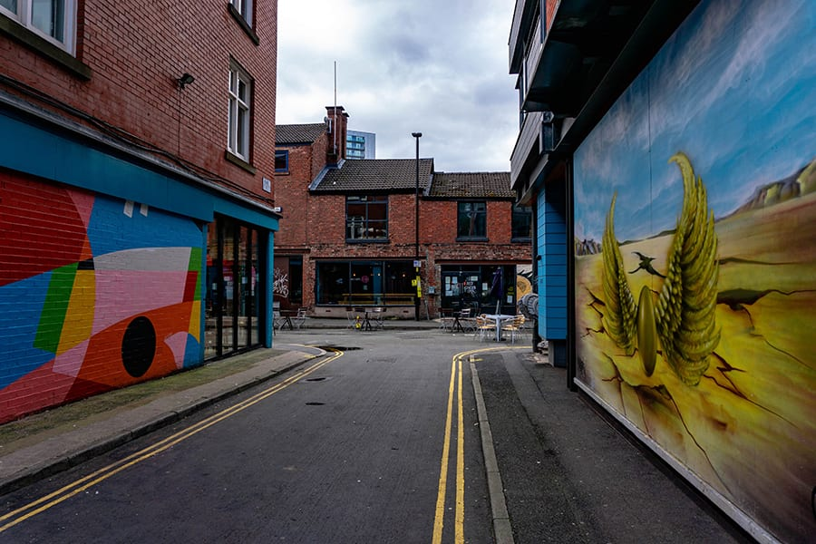 streets in Manchester with painted walls - the left is abstract colours and the right has a golden snitch on a landscape of yello