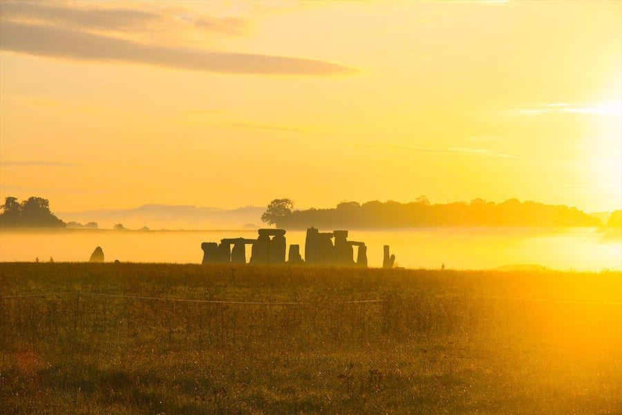 the standing stones of Stonehenge at dawn in yellow light with mist on the surrounding fields