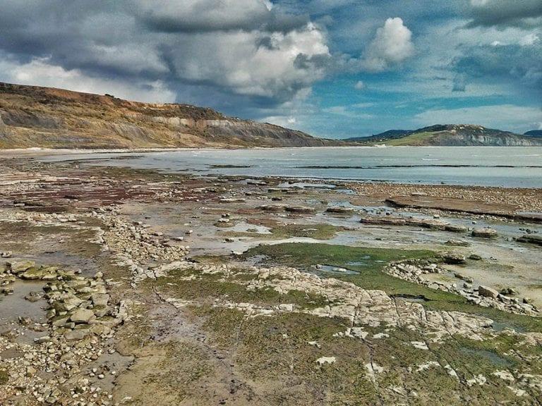 Lyme Regis beach looking over rock pools towards the sea