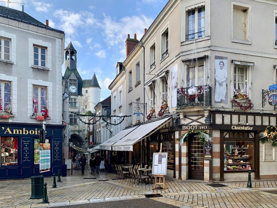 French town of Amboise with cobbled streets with shops and a church with turrets in the background