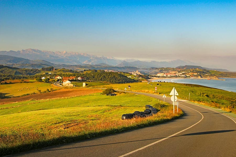 road sweeping round to the left and down to a village with grass fields on the left, sea on the right and mountains in the background