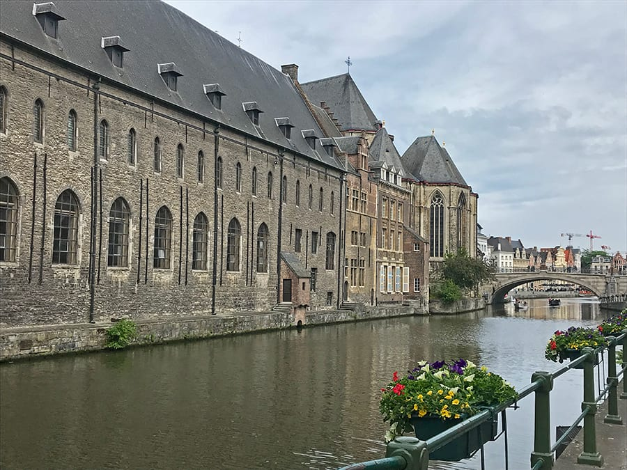 Canal with warehouses in Ghent with flowers baskets on the railings