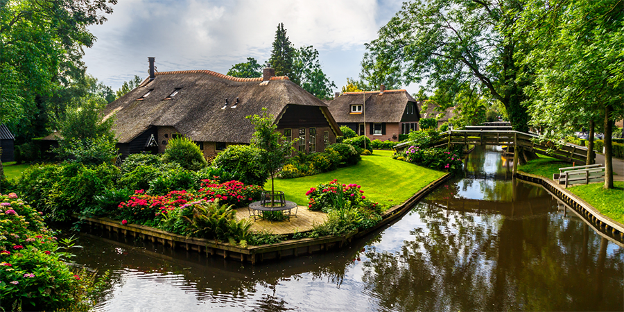 Giethoorn, a hidden gem in the Netherlands. Canal in the foreground with thatched buildings in the middle of green lawns and flowers