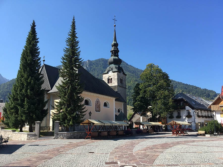 blue skies above a church in Kranjska Gora with cobbled street in front