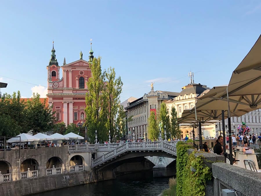 Ljubljana with the river running through the middle and a bridge over it, with buildings in the background