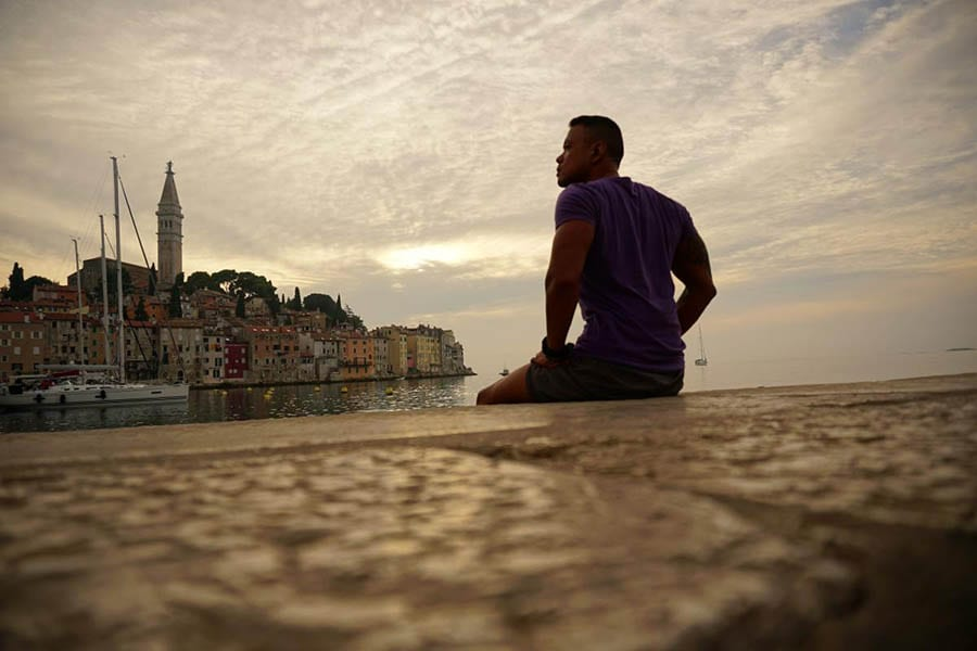Man sitting on a dock looking out over the water towards Rovinj