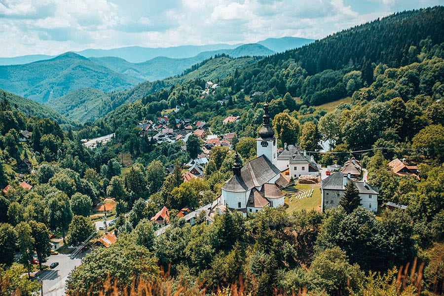 view down a wooded valley with a the roofs of the village of Spania Dolina in the foreground