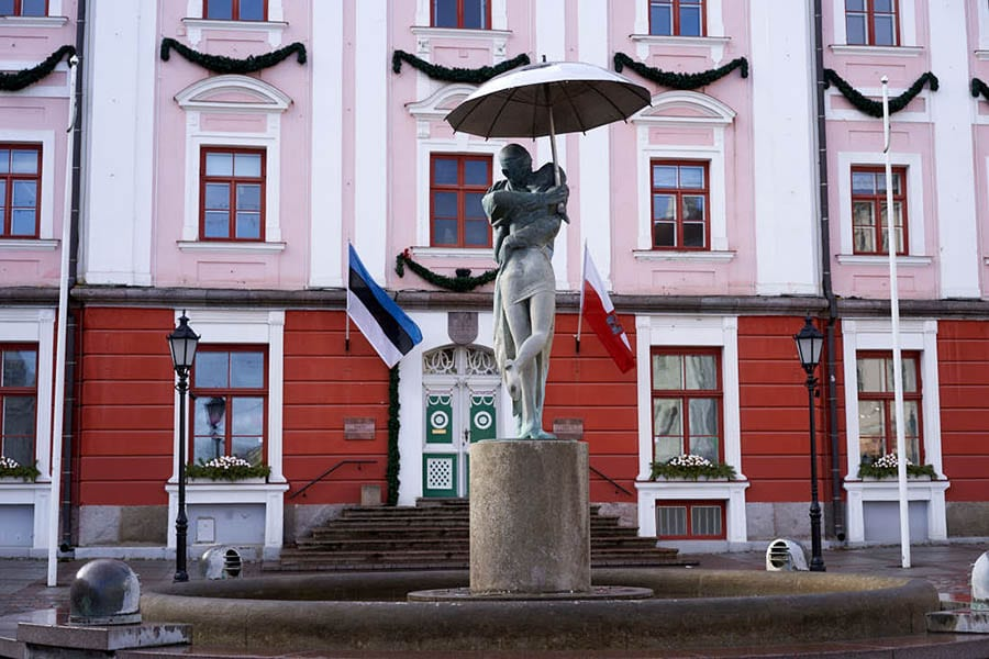 Tartu Town Hall Square with pink and red building behind a fountain with a sculpture of a couple wrapped around each other kissing with the man holding an umbrella above them