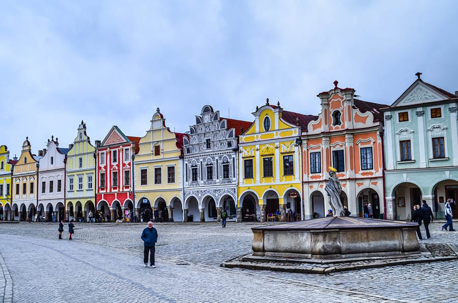 street in Telč of colourful houses in yellow, orange, pink red, grey and green. Each house front has a different shaped facades.