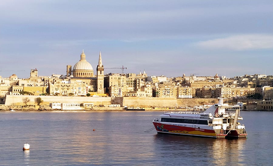 The skyline of Valletta, with cream coloured buildings on the shoreline and a domed building in the background. A ferry boat it anchored in the sea