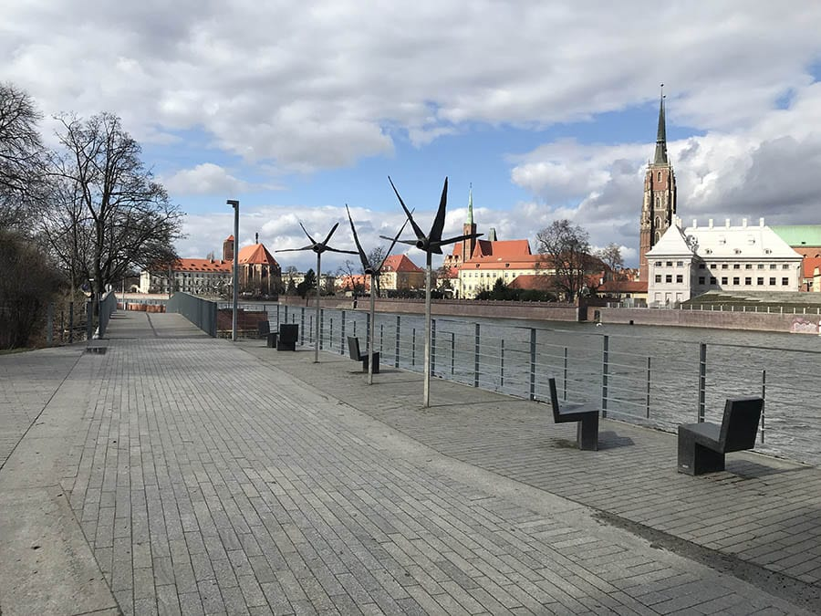 Wroclaw, a hidden gem in Poland - image shows a riven with walkway to the left and churches and other red roofed buildings on rightt